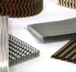 Assortment of aluminum, copper, and stainless steel folded fin stacks in wavy, lanced offset and straight fin configurations